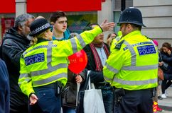 Personnes de aide de Madame Police à Londres, R-U photographie stock libre de droits