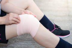 Personnes de femme ou femme asiatiques de sport portant la courroie de genou de soutien ou d'athlète de genou pour diminuer la do photographie stock libre de droits