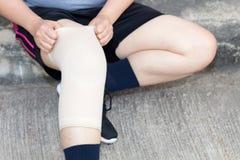 Personnes de femme ou femme asiatiques de sport portant la courroie de genou de soutien ou d'athlète de genou pour diminuer la do photo libre de droits