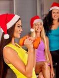 Personnes de groupe utilisant le chapeau de Santa tenant des haltères Photo stock
