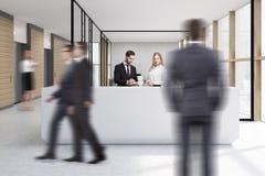 Personnes de marche dans le bureau avec la réception blanche Photo stock
