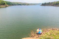 Personnes de pêche à la ligne s'asseyantes avec une canne à pêche Photographie stock