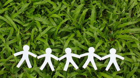 Personnes de papier dans une ligne avec le fond d'herbe verte Photo stock