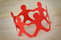 Personnes de papier en cercle tenant des mains - conce de travail d'équipe et d'amour Photos stock