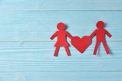Personnes de papier rouges tenant le coeur sur le fond en bois bleu Photos libres de droits