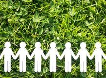 Personnes de papier sur le backgrund d'herbe verte Photo stock