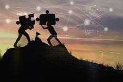 Personnes de silhouette aidant à relier le puzzle Photo stock