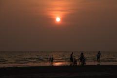 Personnes de silhouette jouant sur la plage Image stock