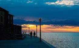 Personnes de silhouette marchant près de la mer au coucher du soleil Photos libres de droits