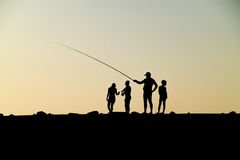 Personnes de silhouette sur le coucher du soleil Photographie stock libre de droits