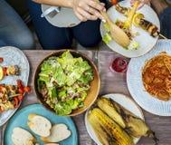 Personnes diverses mangeant de la nourriture ensemble Photos stock