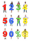 Personnes diverses tenant le nombre et le signe Photographie stock libre de droits