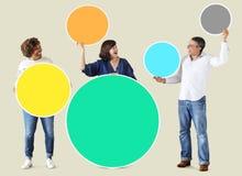Personnes diverses tenant les cercles vides colorés Photographie stock libre de droits