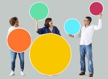 Personnes diverses tenant les cercles vides colorés Photographie stock