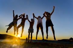 Personnes drôles heureuses sautant dans le coucher du soleil Photographie stock libre de droits
