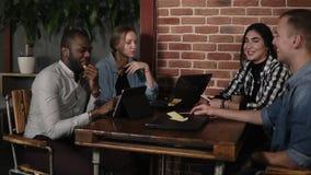 Personnes emballées mélangées de jeunes à l'aide des ordinateurs portables comprimés et smartphones se reposant sur le lieu de tr banque de vidéos