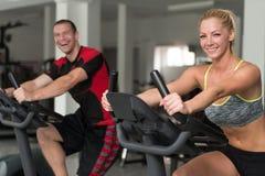 Personnes en bonne santé sur la bicyclette dans le gymnase de forme physique Images stock