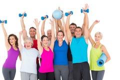 Personnes enthousiastes avec l'équipement d'exercice soulevant des mains image stock