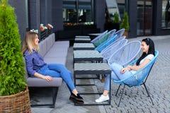 Personnes féminines avec du charme s'asseyant au café de rue dehors Photo libre de droits