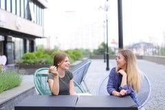 Personnes féminines de sourire s'asseyant au café de rue dehors Photo stock