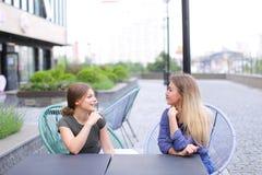 Personnes féminines gaies s'asseyant au café de rue dehors Photo stock