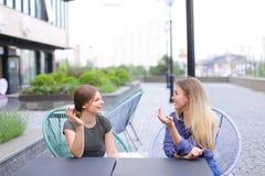 Personnes féminines heureuses s'asseyant au café de rue dehors Images stock
