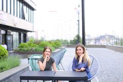 Personnes féminines s'asseyant au café de rue dehors Images libres de droits