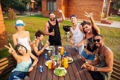 Personnes gaies ayant l'amusement et mangeant à la table dehors Photos stock
