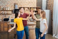 Personnes gaies enthousiastes touchant leurs mains tout en jouant un jeu Image libre de droits