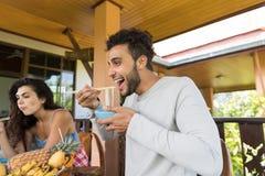 Personnes gaies goûtant les nouilles asiatiques mangeant avec des amis de baguettes ensemble se réunissant et communiquant Image libre de droits