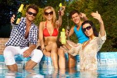 Personnes gaies par la piscine Photographie stock