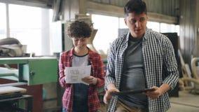 Personnes gaies parlant dans l'atelier en bois marchant avec les documents sur papier de comprimé et banque de vidéos
