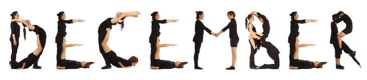 Personnes habillées par noir formant le mot DÉCEMBRE Image stock