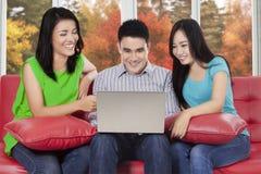 Personnes heureuses à l'aide de l'ordinateur portable au divan Photos stock