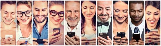 Personnes heureuses à l'aide du téléphone intelligent mobile photographie stock libre de droits