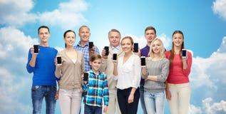 Personnes heureuses avec des smartphones au-dessus de ciel et de nuages Images stock