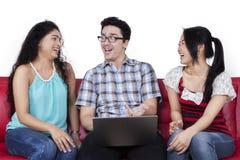 Personnes heureuses avec l'ordinateur portable parlant ensemble Image stock
