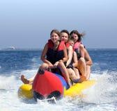 Personnes heureuses ayant l'amusement sur le bateau de banane Photographie stock