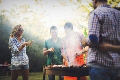 Personnes heureuses ayant le camping et ayant la partie de BBQ Photographie stock