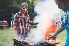 Personnes heureuses ayant le camping et ayant la partie de BBQ Images libres de droits