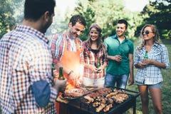 Personnes heureuses ayant le camping et ayant la partie de BBQ Images stock
