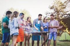 Personnes heureuses ayant le camping et ayant la partie de BBQ Photos stock