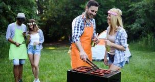 Personnes heureuses ayant le camping et ayant la partie de BBQ Photographie stock libre de droits