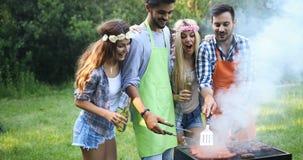 Personnes heureuses ayant le camping et ayant la partie de BBQ Photo libre de droits