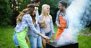 Personnes heureuses ayant le camping et ayant la partie de BBQ Image libre de droits