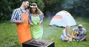 Personnes heureuses ayant le camping et ayant la partie de BBQ Photo stock
