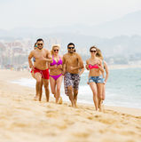 Personnes heureuses courant à la plage Photos stock