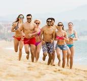 Personnes heureuses courant à la plage Photo libre de droits