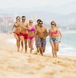 Personnes heureuses courant à la plage Images stock