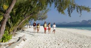Personnes heureuses courant le long de la plage, de l'homme de course de mélange et des touristes de groupe de femme des vacances banque de vidéos
